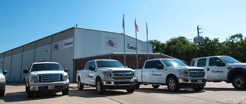 Front of Curflo Manufacturing Building with Curflo Pick-Up Trucks Parked